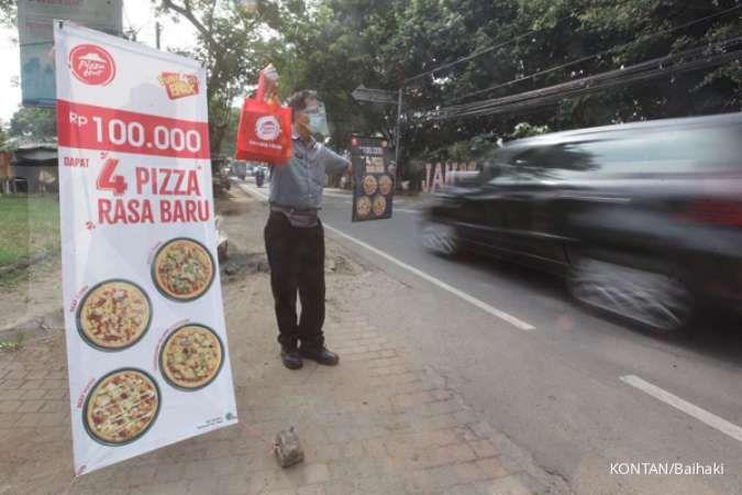 Karyawan Pizza Hut menawarkan dagangannya di pinggir jalan raya Muhtar, Depok, Jawa Barat, Jumat (16/10/2020). November ini Scottish Oriental memborong saham pengelola pizza hut, PT Sarimelati Kencana Tbk (PZZA). KONTAN/Baihaki/16/10/2020