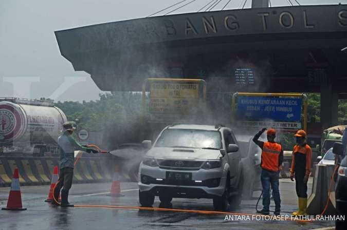 Sejumlah petugas menyemprotkan cairan disinfektan ke kendaraan yang keluar di Pintu Tol Serang Timur, di Serang, Banten, Minggu (19/4/2020). Pemda setempat memberlakukan pemeriksaan kesehatan bagi setiap orang dan penyemprotan disinfektan setiap kendaraan