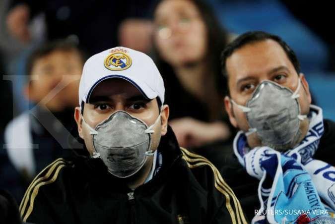 Pendukung Real Madrid mengenakan masker