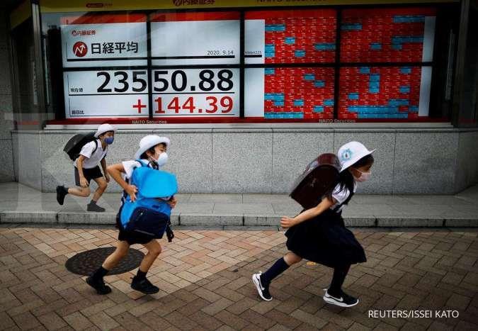 Passersby wearing masks run past an electronic board showing Japan's Nikkei average outside a brokerage