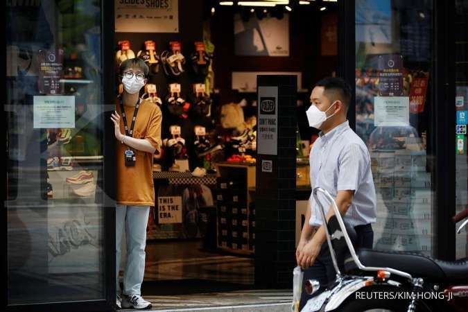 A shop assistant waits for a customer at Myeongdong shopping district which is nearly empty amid the coronavirus disease (COVID-19) pandemic in Seoul, South Korea, August 24, 2020.