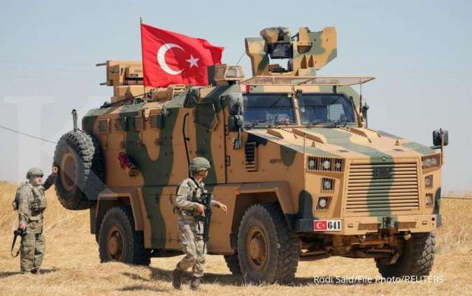 Seorang tentara Turki berjalan di samping kendaraan militer Turki selama patroli gabungan AS-Turki, dekat Tel Abyad, Suriah 8 September 2019.