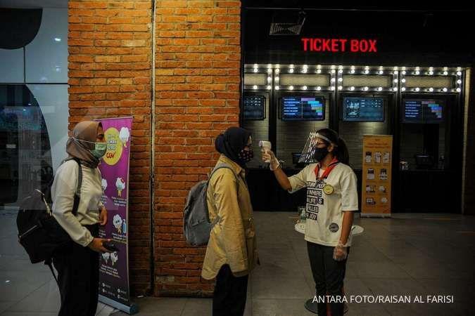 Petugas memeriksa suhu tubuh pengunjung yang akan menonton film. ANTARA FOTO/Raisan Al Farisi/pras.
